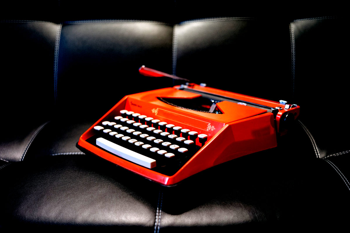 personal branding tomato red typewriter sitting on a black leather couch